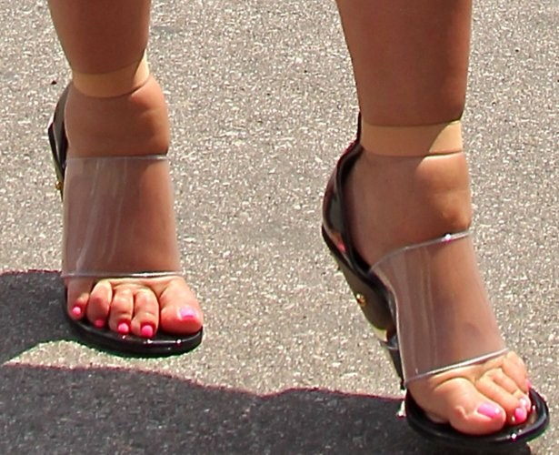 Kim's squashes Feet into Plastic Shoes